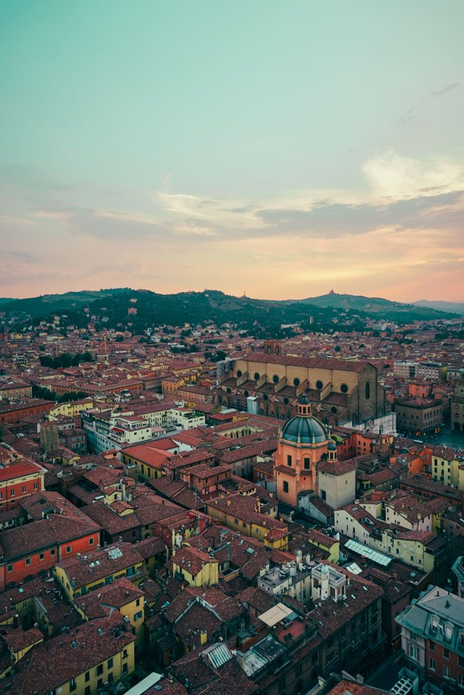 view of the city of bolonga from the tower of bologna at sunset