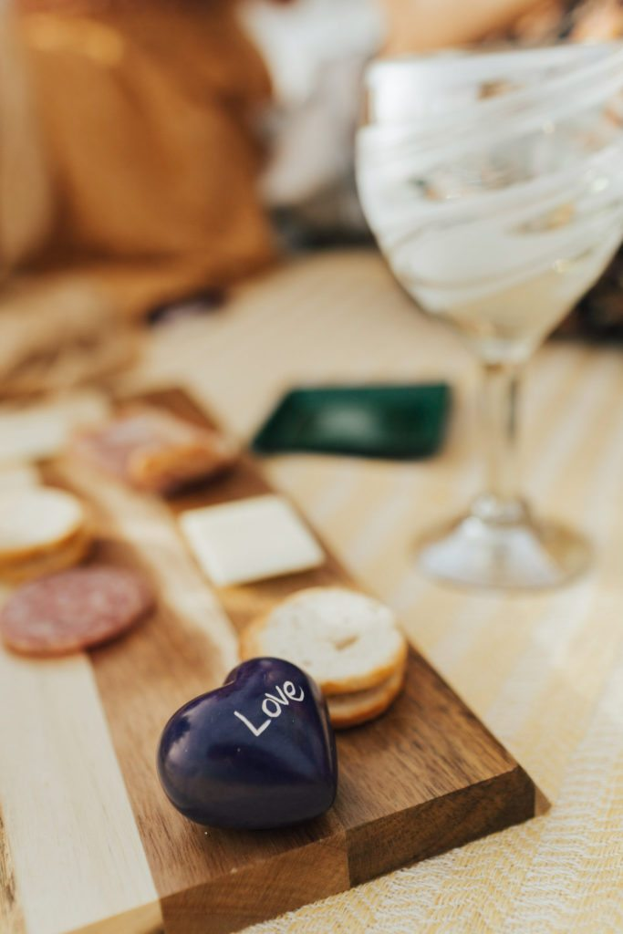 Globe In Sandstone Word Heart on the cheese board with the Hand Blown Wine Glass standing next to it