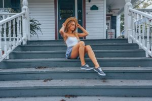 Megan Rae sitting on blue stairs in front of a white house in flowy blue shorts, white crop tank top, straw hat, and star printed sneakers