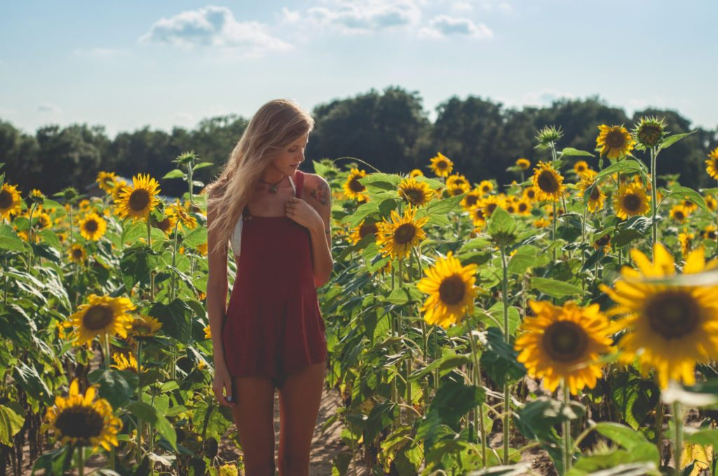 Janna Rasch of Drishti Aesthetics in red romper in sunflower field