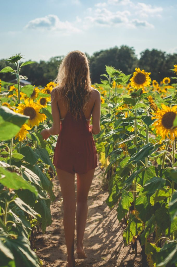 Janna Rash in red romper walking through holland farms sunflower field in milton, florida