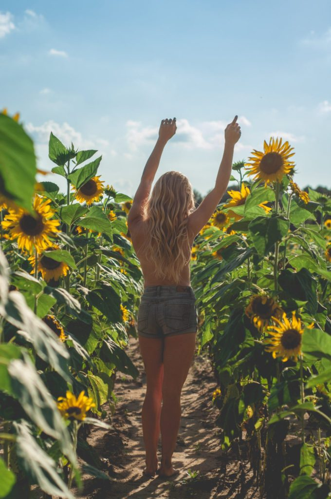 Megan Rae in blue jean shorts with arms above head in a sunflower field with her back facing the camera