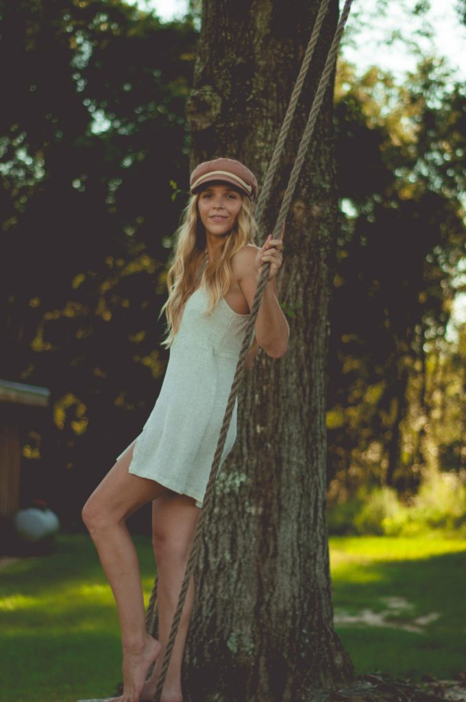 Megan Rae on wooden tree swing in wrap dress and pink hat