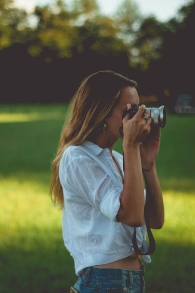 Chelsea Owens in a white tied button up takin photos