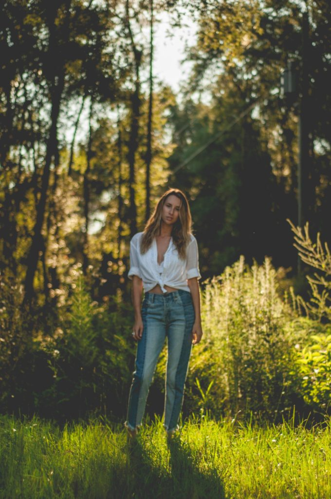 Chelsea Owens in white tied button up and blue jeans in the golden light