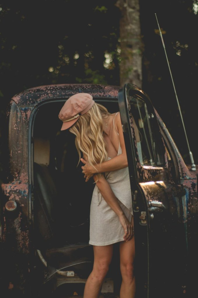 Megan Rae standing in an old truck wearing a wrap dress and pink hat