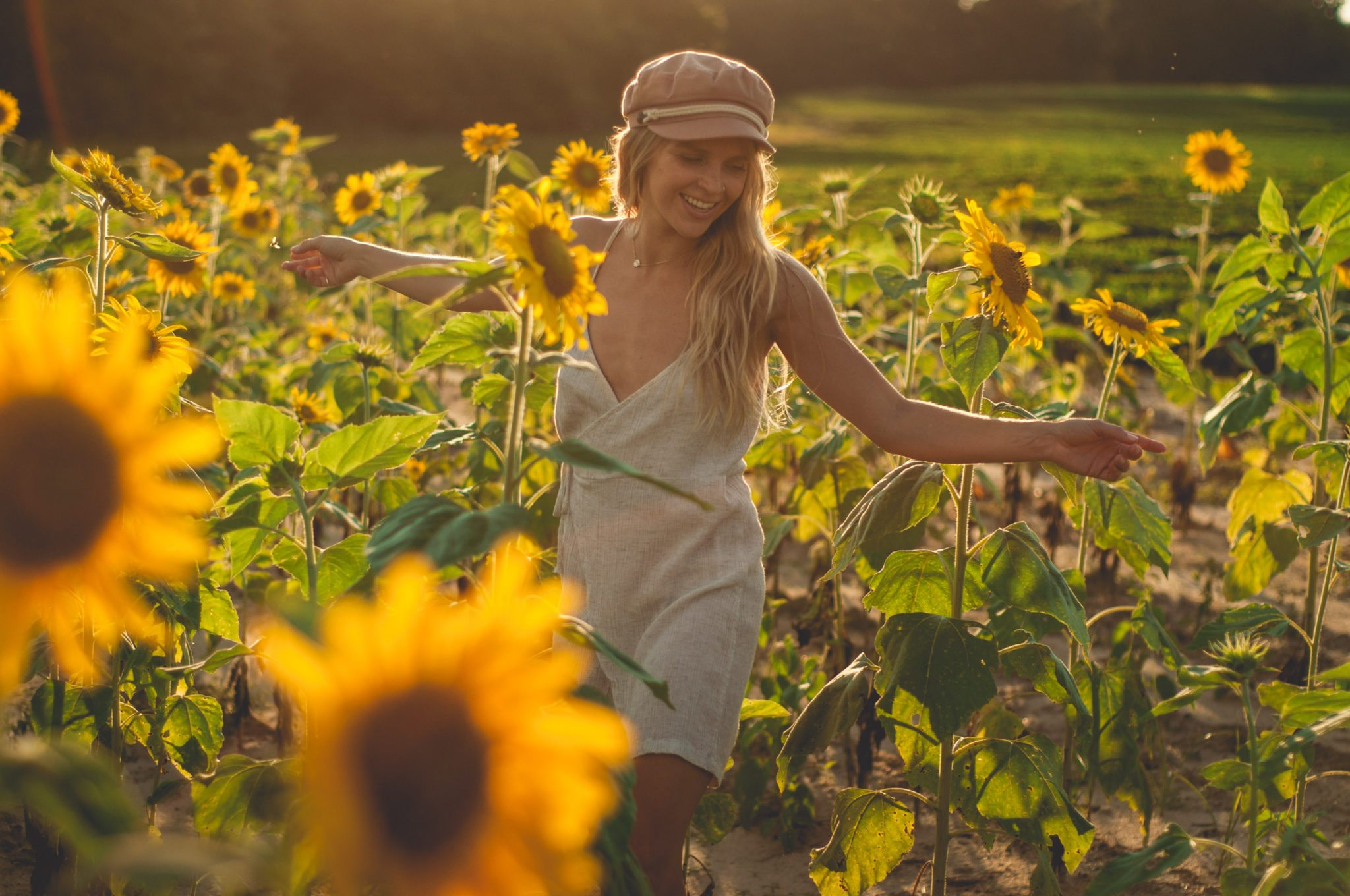 Megan Rae dancing through Holland Farm sunflower fields in July at golden hour