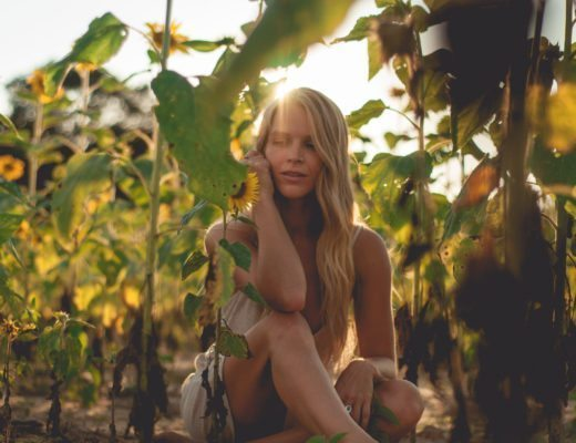 Megan Rae sitting in the flower field in a beige wrap dress with light waves in her hair