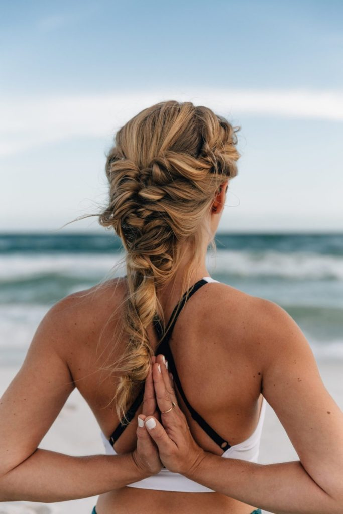 Megan Rae practicing Pashchima Namaskarasana facing the Gulf of Mexico