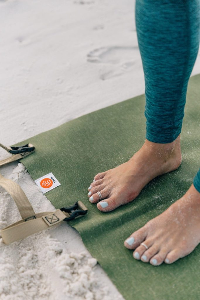 Megan Rae stading on her green YOGO yoga mat on Pensacola Beach