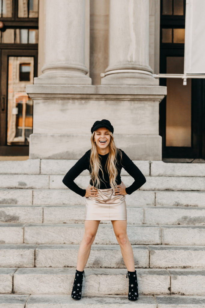 Megan Rae standing in front of the art museum on Palafox Street Downtown Pensacola wearing black boots with silver stars, a gold leather skirt, black long sleeve and black hat