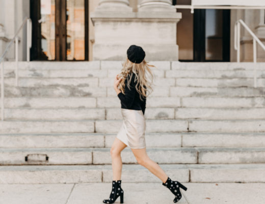 Megan Rae walking in front of the art museum on Palafox Street Downtown Pensacola wearing black boots with silver stars, a gold leather skirt, black long sleeve and black hat