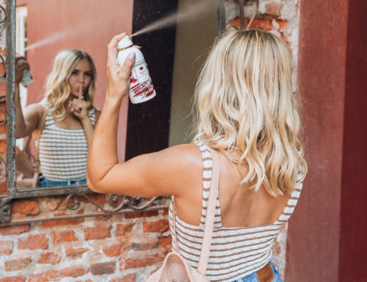 Megan Rae spraying Pantene Never Tell dry shampoo from the Pantene Waterless Collection into her short, beach wave hair in a New Orleans courtyard mirror. Megan is wearing a brown and white striped tank top with high waisted Levi jeans and a light tan backpack purse.