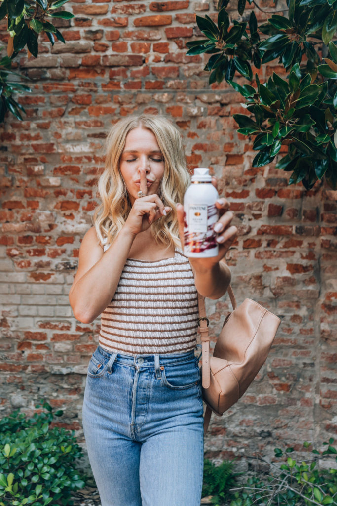 Megan Rae is holding out her Pantene Waterless Collection Never Tell Dry Shampoo and making a sshh face with her finger over her lips and eyes closed. Megan has shoulder length blonde waves in her hair. She is also wearing a brown and white striped tank top with high waisted Levi jeans and a light tan backpack purse.